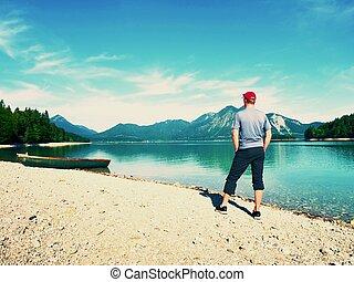 Tall man walks at bench on lake shore and looks
