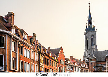 Tall medieval bell tower rising over the street with old ...