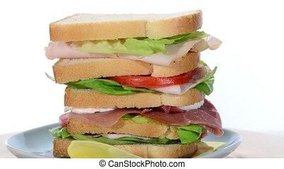 tall sandwich with ham, chicken, cheese and tomato