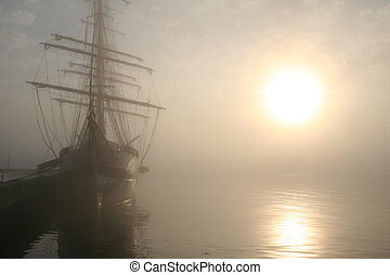 Tall ship docked in Halifax harbor on a foggy morning.