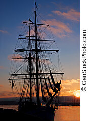 Tall ship silhouette at sunset at pier