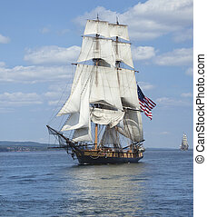 Tall ship with American flag sailing on blue waters - A tall...