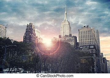 Tall skyscraper in New York city, sunrise in background.