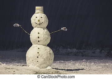 Tall snowman at winter night in the park outdoors.