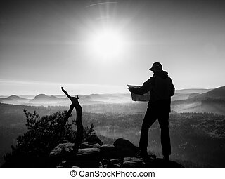 Tall tourist guide looking in paper map. Wild hilly nature