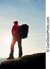 Tall tourist red black sportswear. Sunny evening in rocky mountains. Hiker with big backpack stand on rocky view point