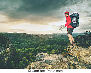 Tall tourist with big backpack looking in paper map. Wild hilly nature