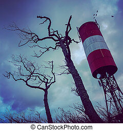 Tall tower and dry trees against overcast sky