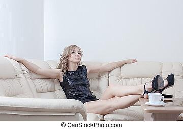 tall woman in black dress relax on sofa