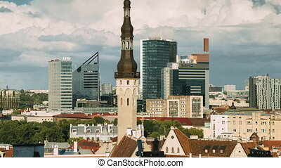 Tallinn, Estonia. Tower Of Town Hall On Background With Modern Urban Skyscrapers. City Centre Architecture. UNESCO World Heritage Site