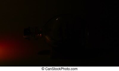 Tallship in glass bottle lit by colorfull searchlight at dark