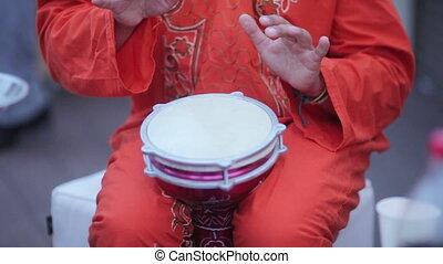 Tam-tam drums on banket - Man plays African drum tam tam