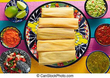 Tamale with corn leaf and sauces guacamole pico de gallo
