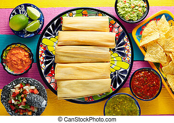Tamale with corn leaf and sauces guacamole pico de gallo