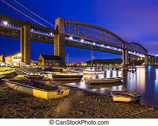 The road and rail bridges over the River Tamar at night with Plymouth in Devon on the far side of the river photographed at Saltash Cornwall