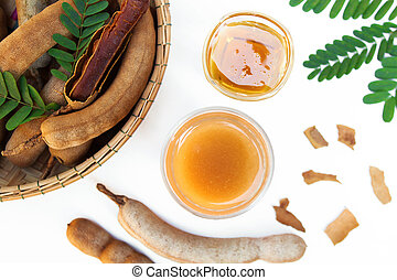 Tamarind and tamarind juice with honey on white background