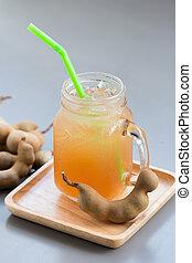 tamarind juice with sugar on gray table.