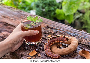 Tamarind juice - Woman holds delicious sweet drink tamarind...