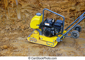 Tamping machine preparation of the ground by vibratory plate...