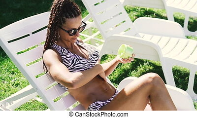 Tan. A woman in a swimsuit smears a sunscreen.