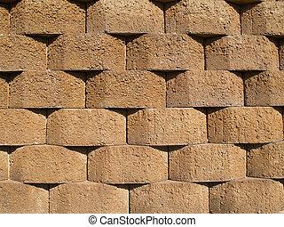 Tan Retaining Wall - Rows of tan stone blocks that make up a...