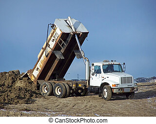 A truck unloading some dirt at a construction site