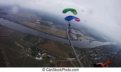 Tandem of skydivers with colorful parachutes balance in sky over green field.