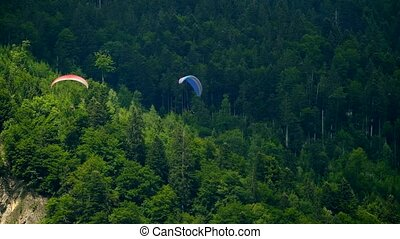 Tandem paragliders flying in the mountains - Tandem...