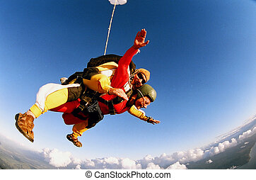 Two people skydiving in tandem from an aeroplane.