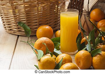 tangerine basket and juice over wood table