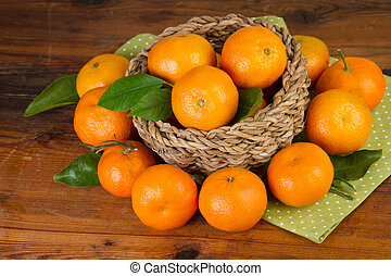 tangerine basket full with green napkin on old wooden background