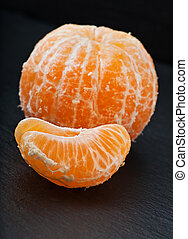 Tangerine fruit on a dark background.