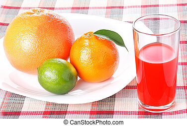 Tangerine, grapefruit and lime on white plate with glass of red orange juice
