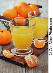 Tangerine juice in glass with fresh fruits on wooden...