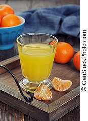 Tangerine juice in glass with fresh fruits on wooden ...