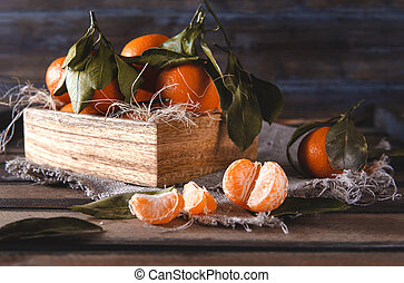 tangerine slices, whole  tangerines in a box on a wooden background