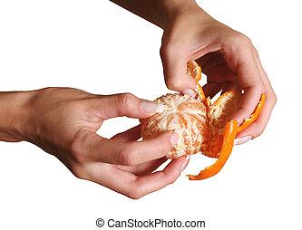 Tangerine - Female hands clean a tangerine on a white...