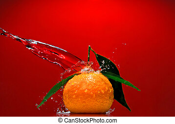 Tangerine with green leaves and water splash on red background