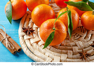 Tangerines and cinnamon on wooden background