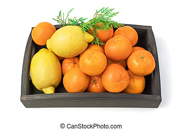 Tangerines and lemons in a box with a coniferous branch, isolated on a white background.