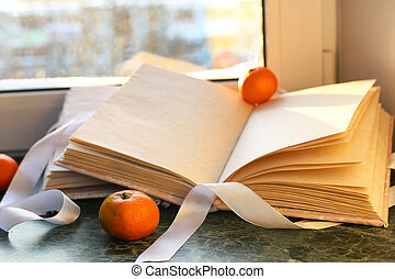 tangerines and vintage books on a marble table by the window