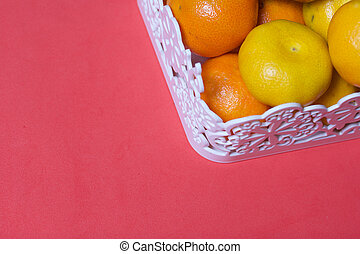 Tangerines in a wicker basket. Against the background of coral color.