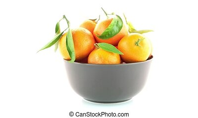 Tangerines on ceramic brown bowl isolated on white...