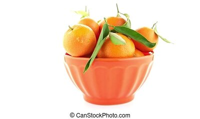 Tangerines on ceramic orange bowl isolated on white...