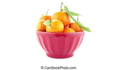 Tangerines on ceramic red bowl isolated on white background