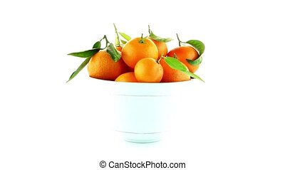 Tangerines on ceramic white bowl isolated on white...