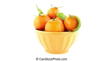 Tangerines on ceramic yellow bowl isolated on white...