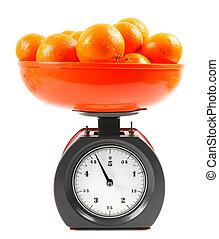 Tangerines on scales on a white background.