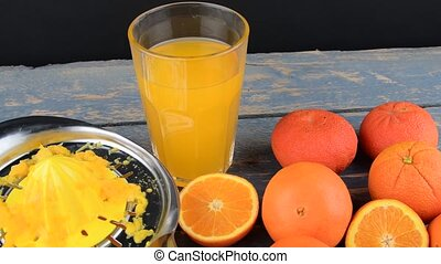 Tangerines, oranges, a glass of orange juice and manual citrus squezeer on blue wooden background. Oranges cut in half
