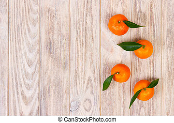 Tangerines with green leaves on wooden background